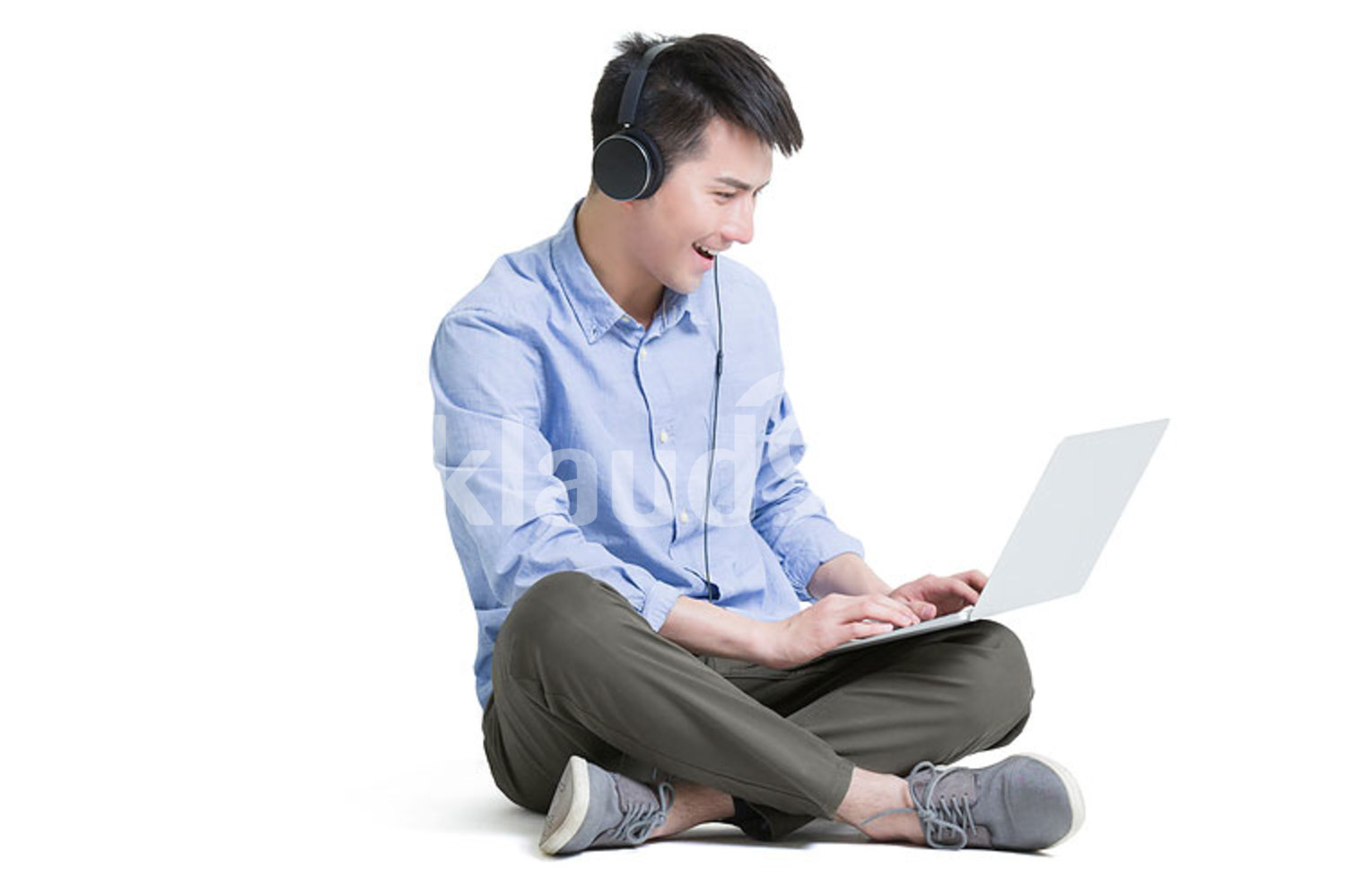 Young Chinese man listening to music with laptop