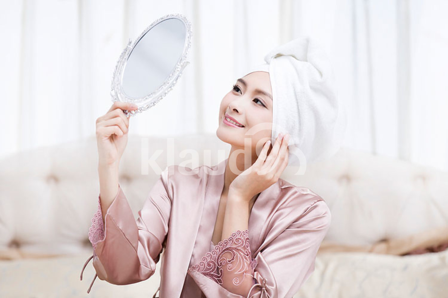 Beautiful young Chinese woman looking into the mirror