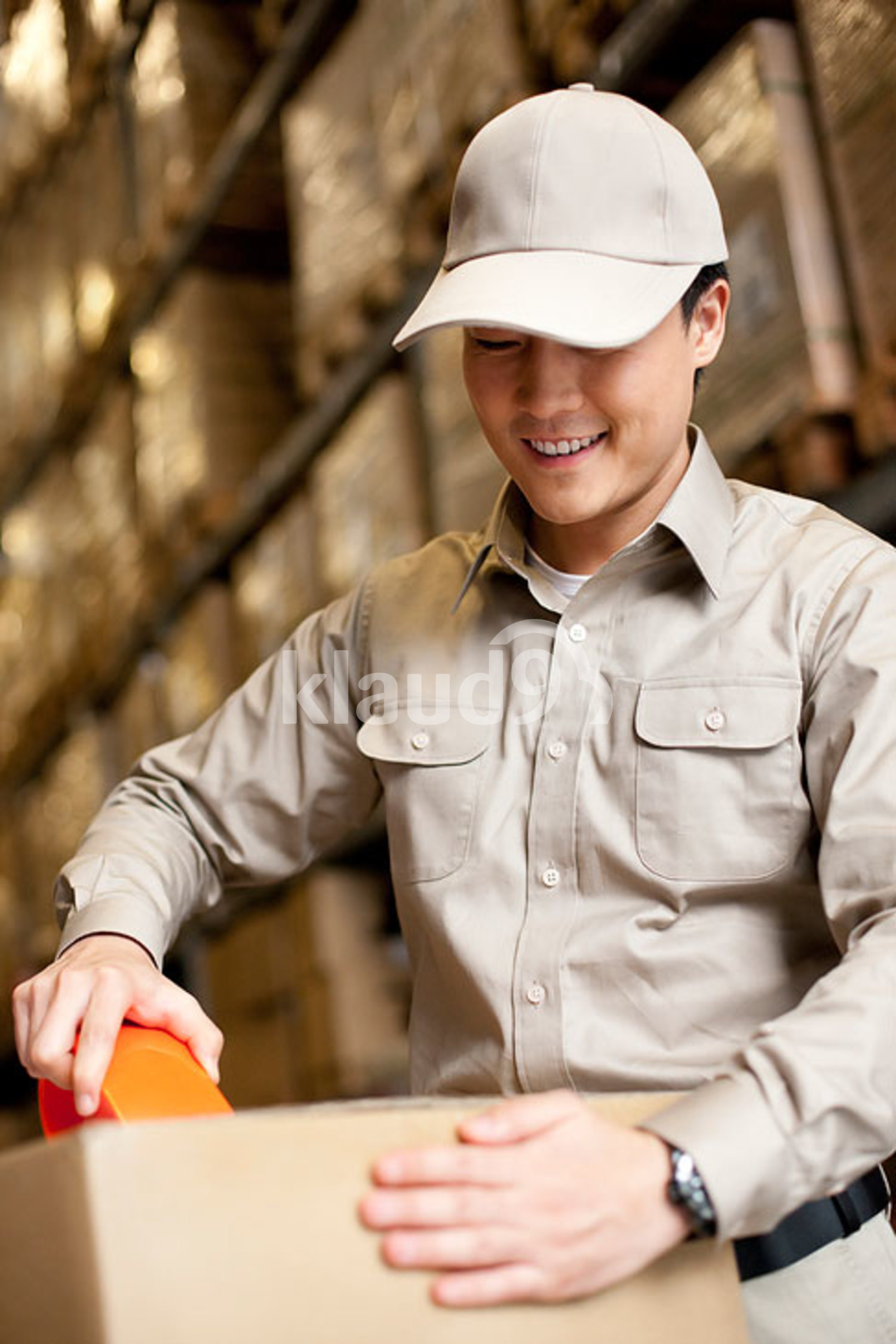Male Chinese warehouse worker packing a box