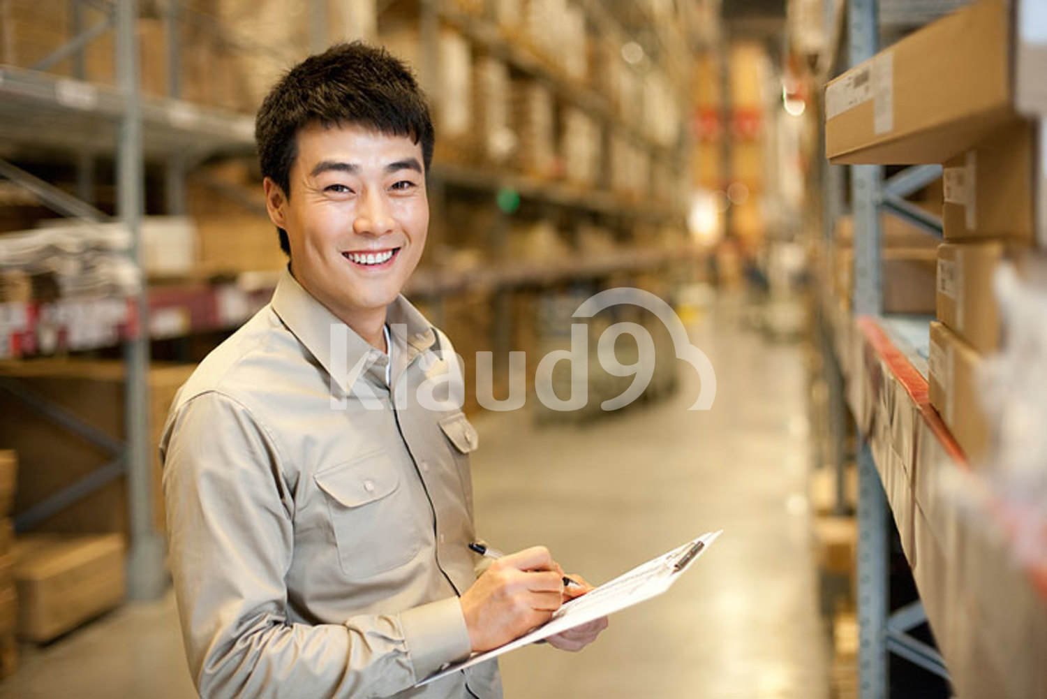 Female Chinese warehouse worker with clipboard and walkie-talke