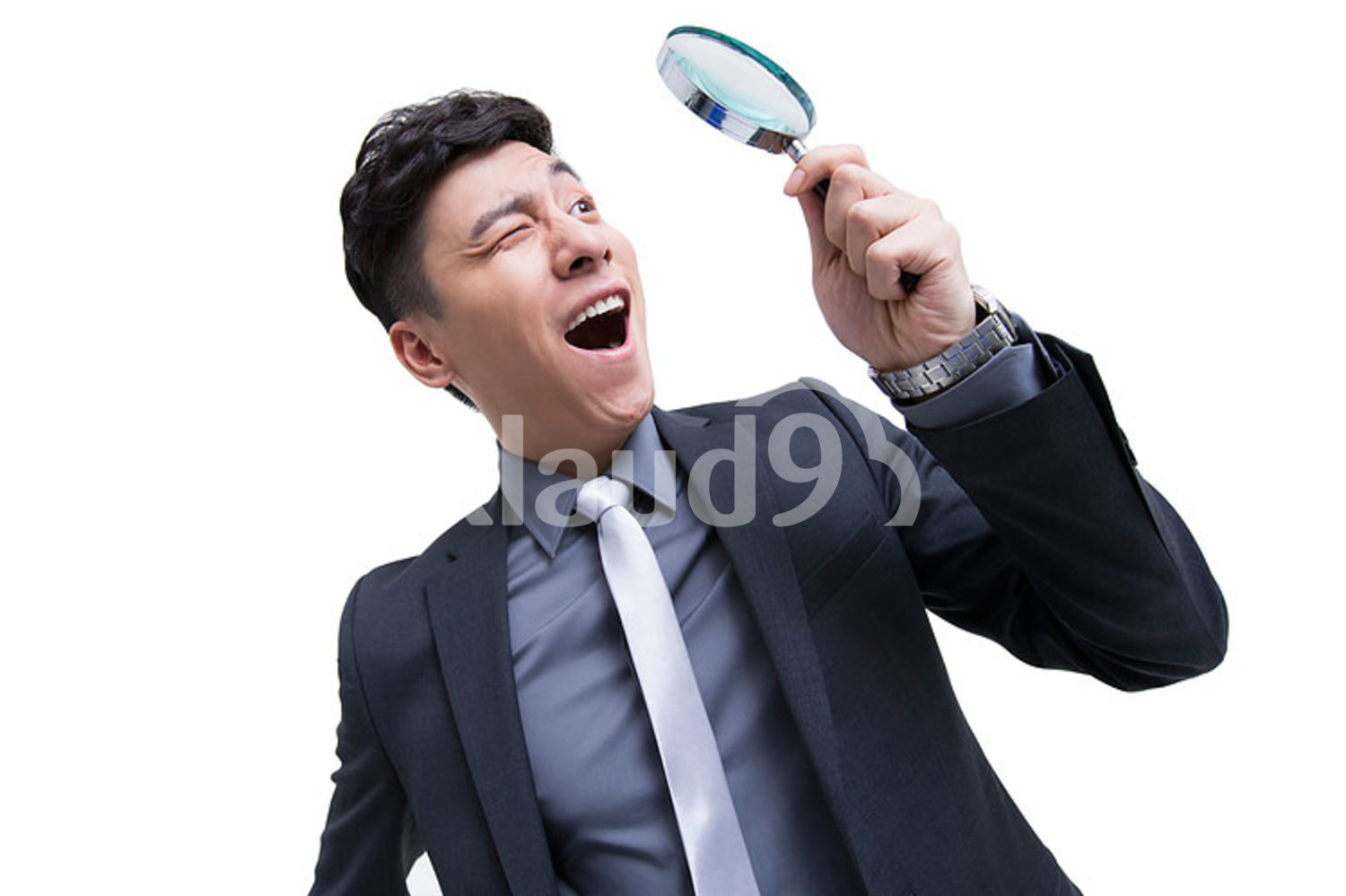 Young Chinese businessman looking through magnifying glass