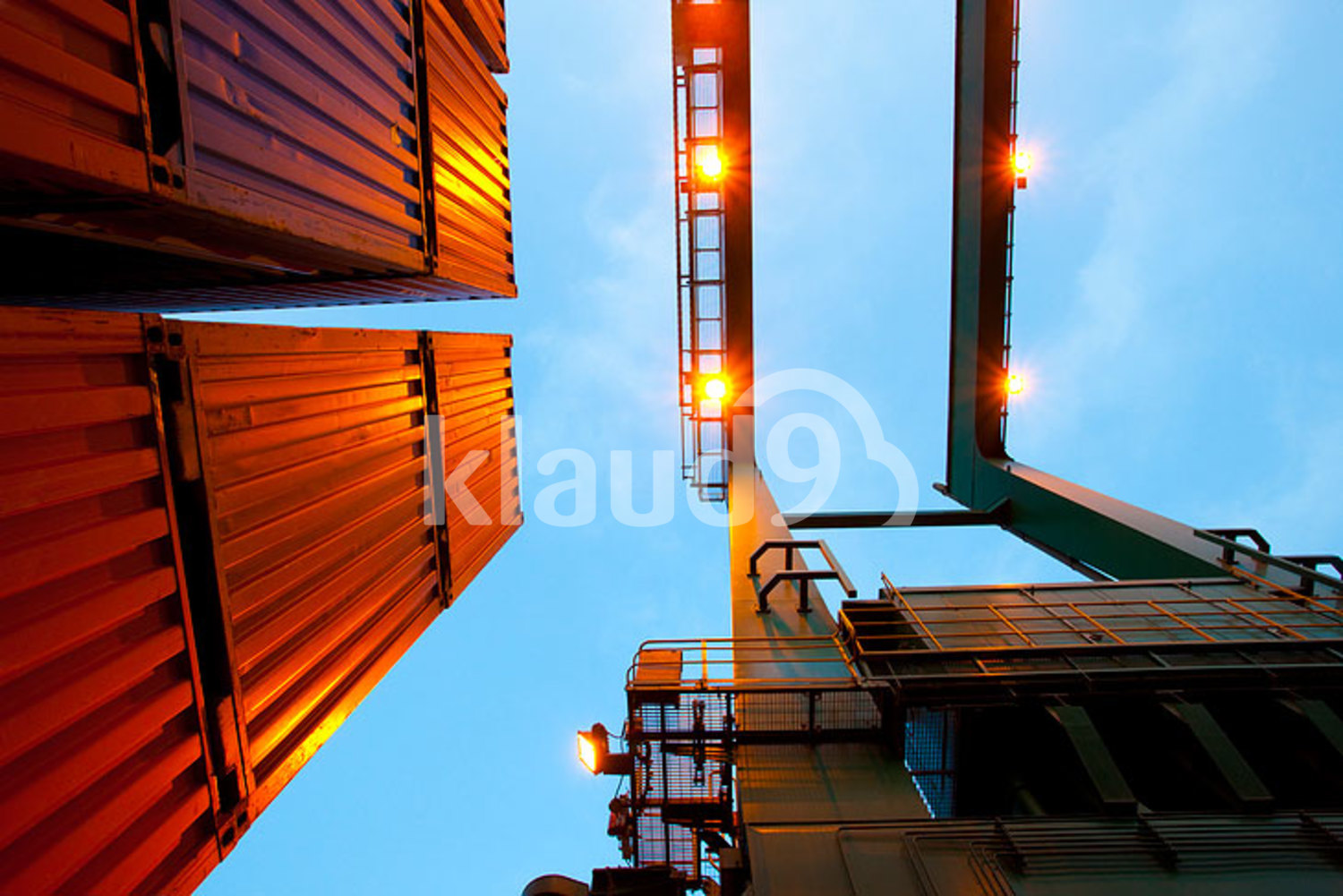 Bottom view of cranes and stack of cargo containers