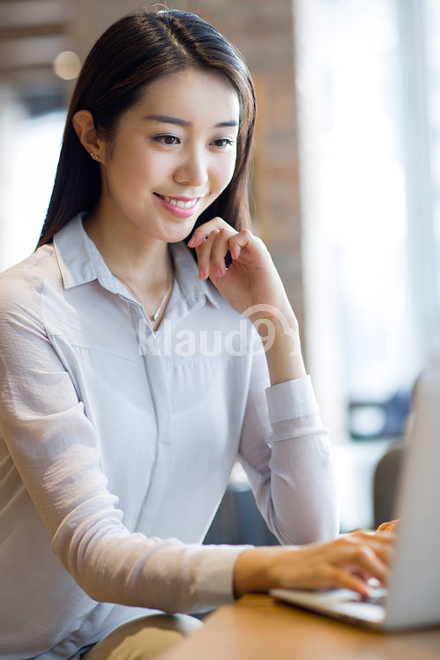 Young Chinese woman working with laptop in café