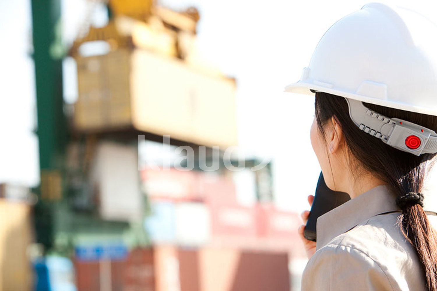 Chinese shipping industry worker directing cranes with her walkie-talkie