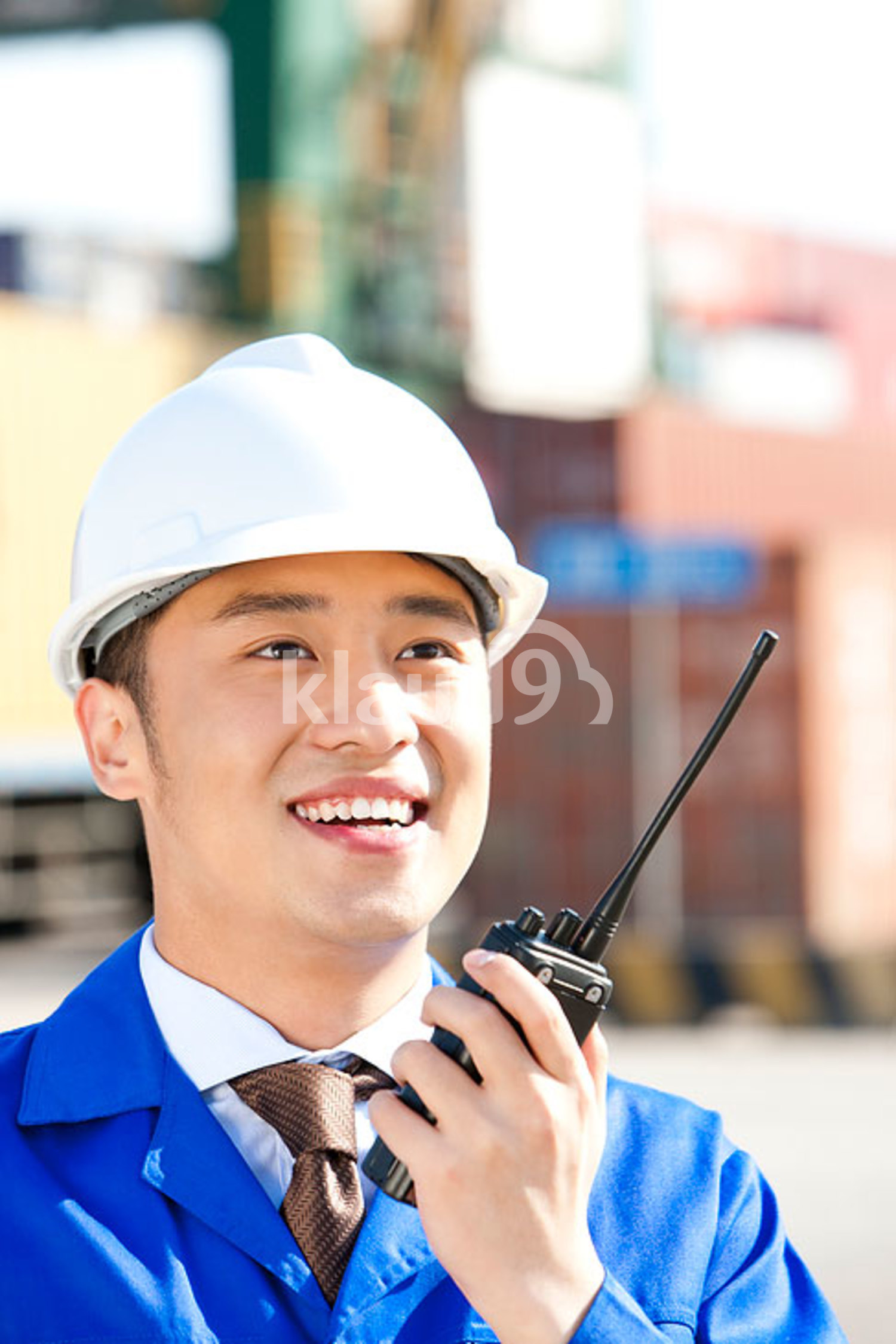Chinese shipping industry manager with a walkie-talkie