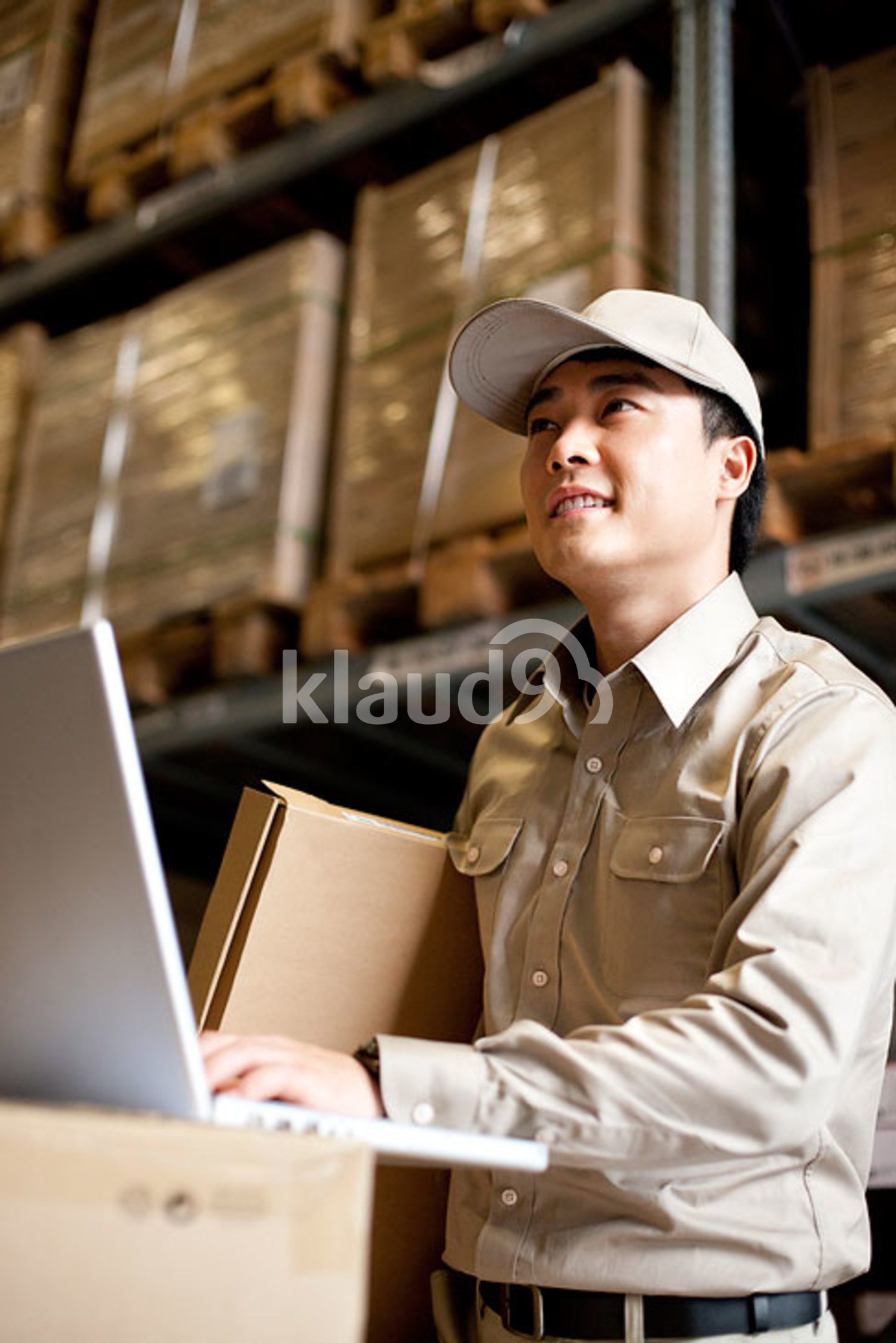 Male Chinese warehouse worker using a laptop