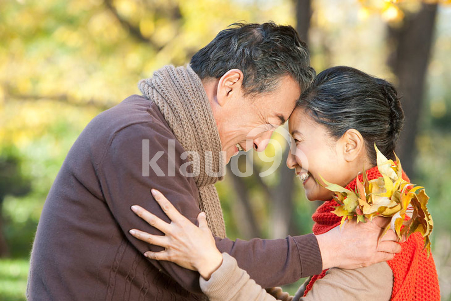Senior Chinese couple smiling face to face in autumn