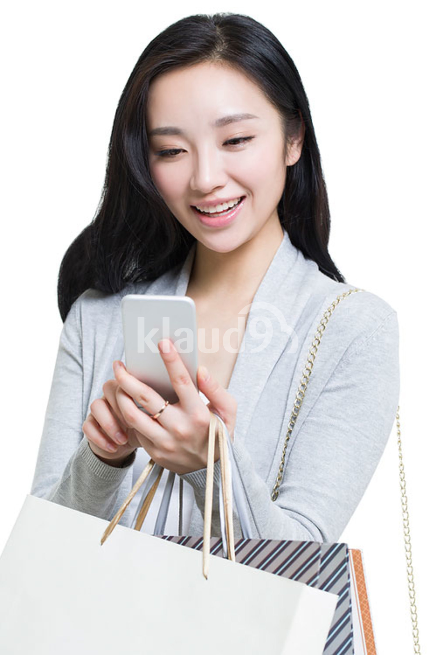 Happy young Chinese woman holding a smart phone and shopping bags