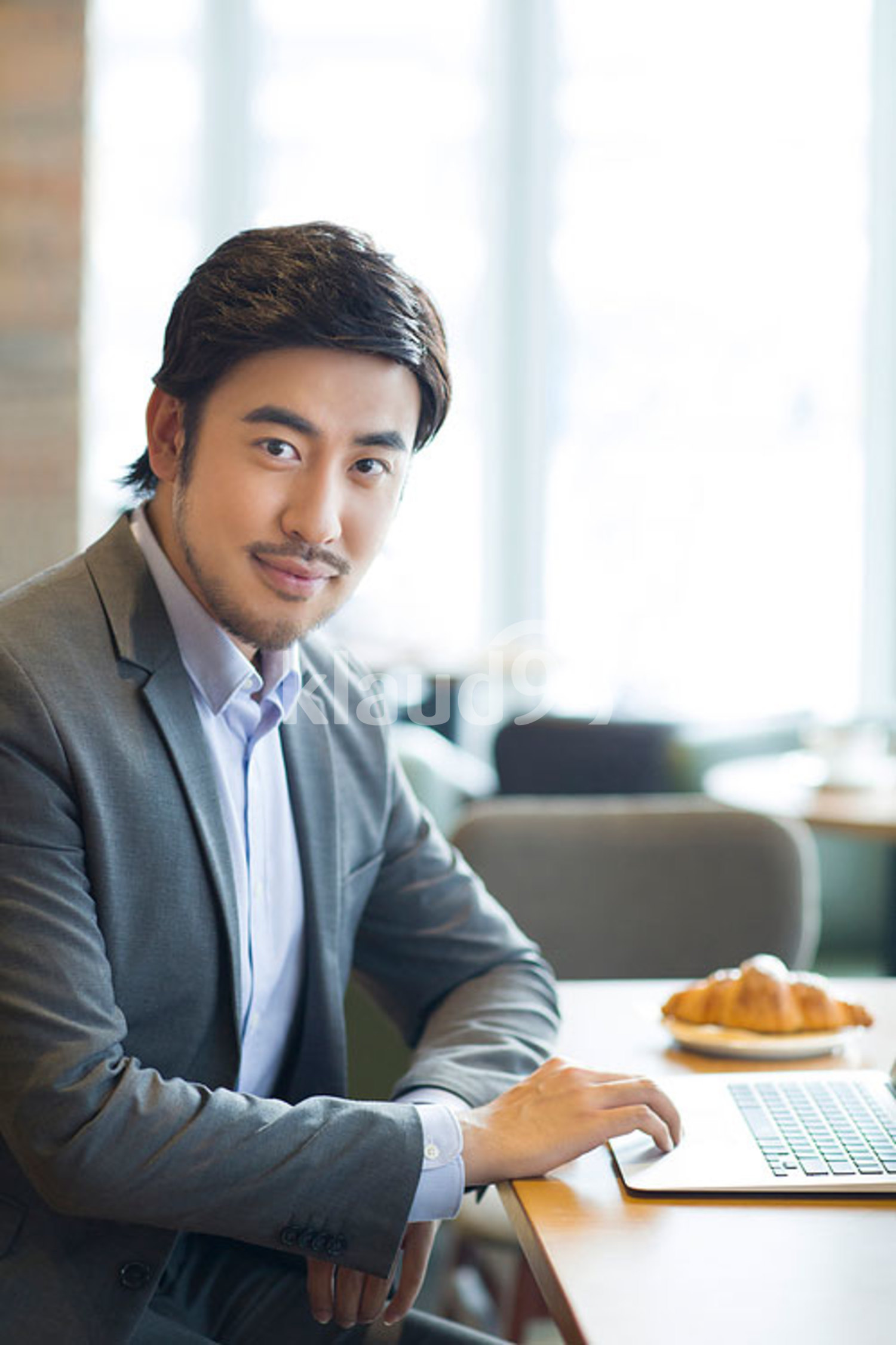 Chinese businessman working with laptop in café