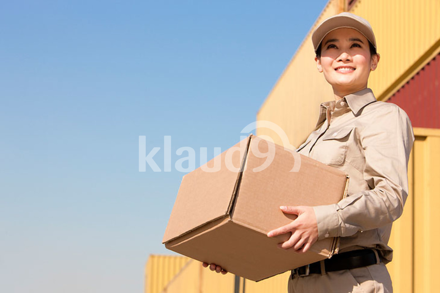 Chinese shipping industry worker carrying a cardboard box