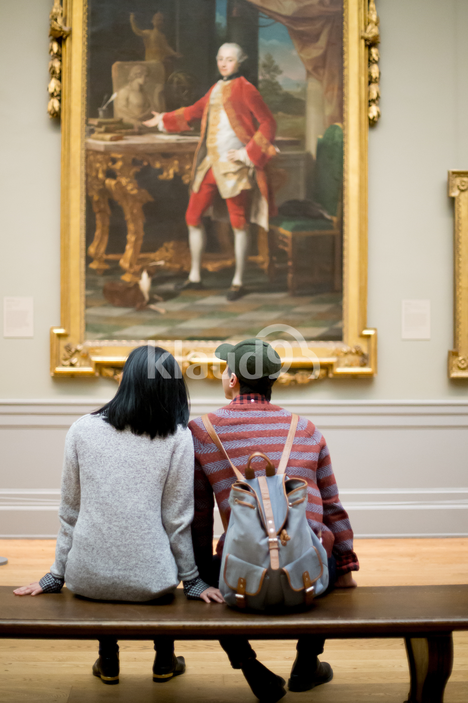 Back view of a couple looking at paintings
