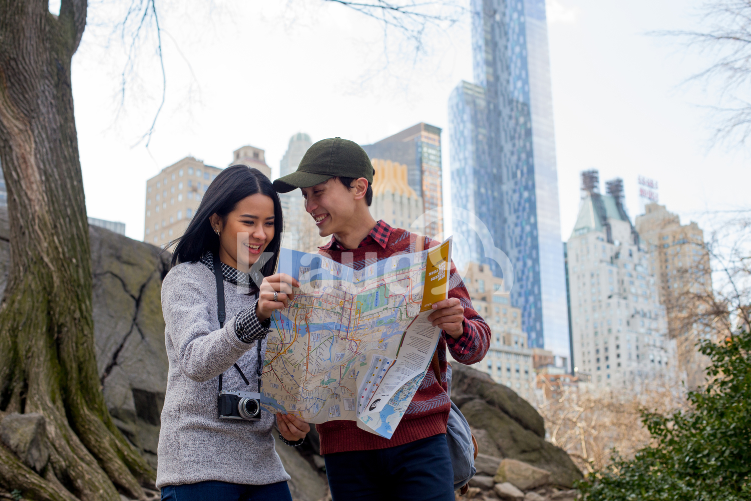 Happy tourists checking directions in Central Park