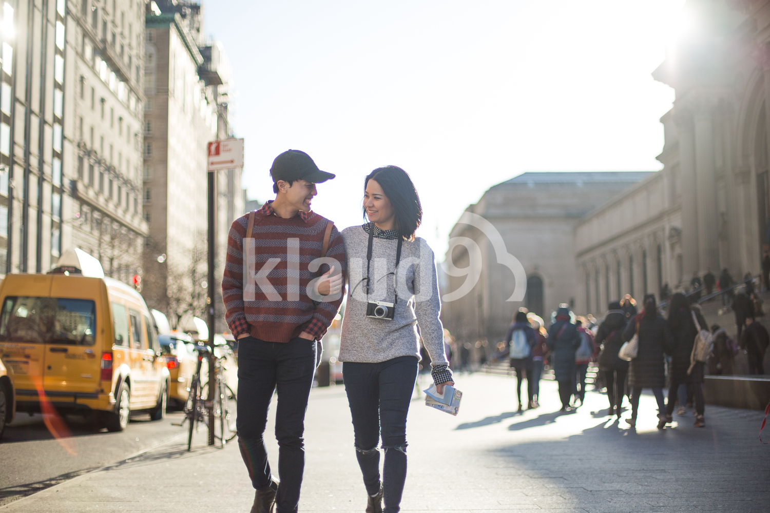 Attractive tourist couple being playful while walking together in front of The Metropolitan Museum of Art
