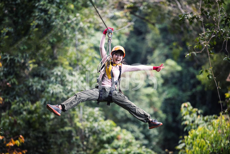 Cheerful Female Tourist on Zip Line