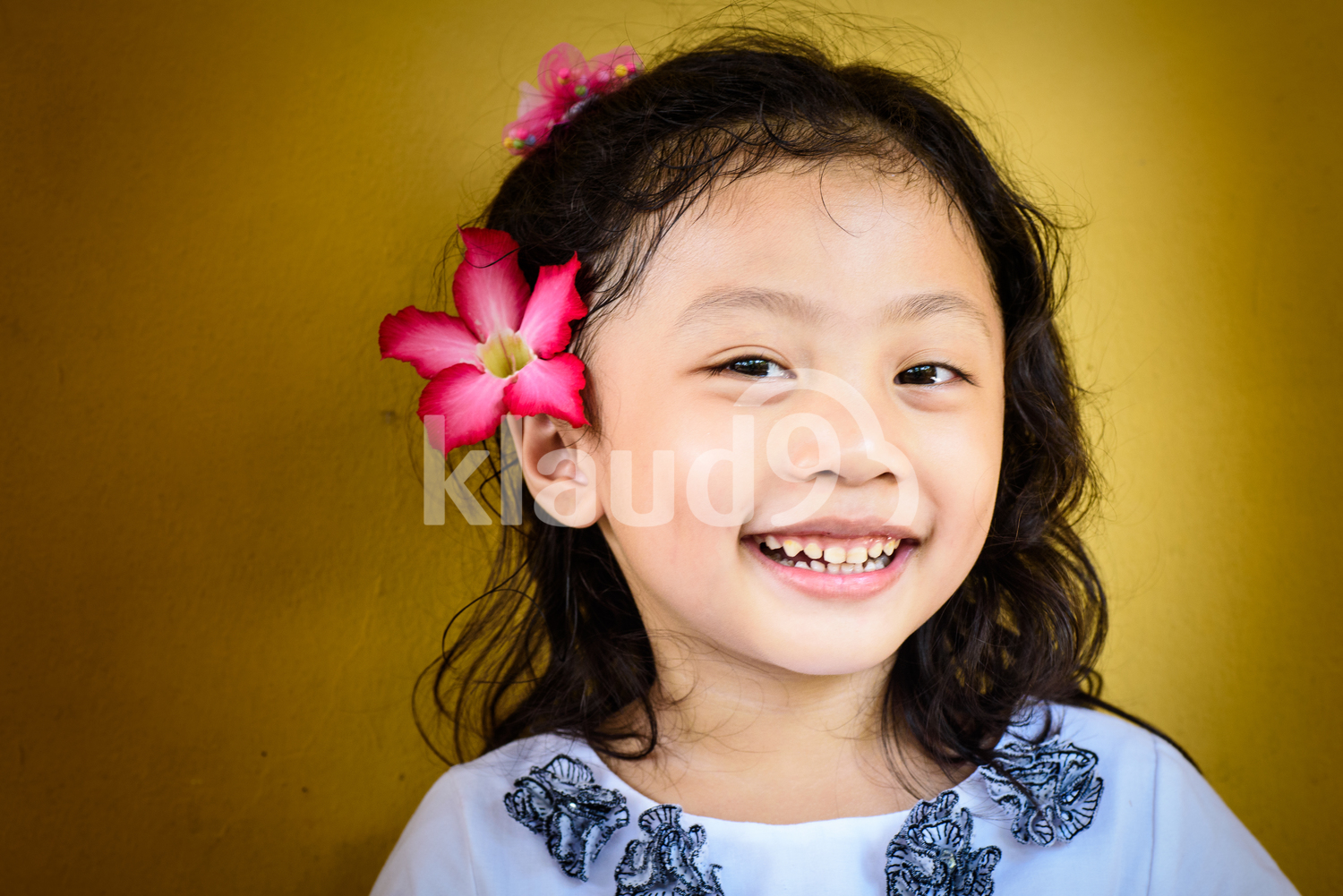 Young girl with flower in hair smiling for the camera