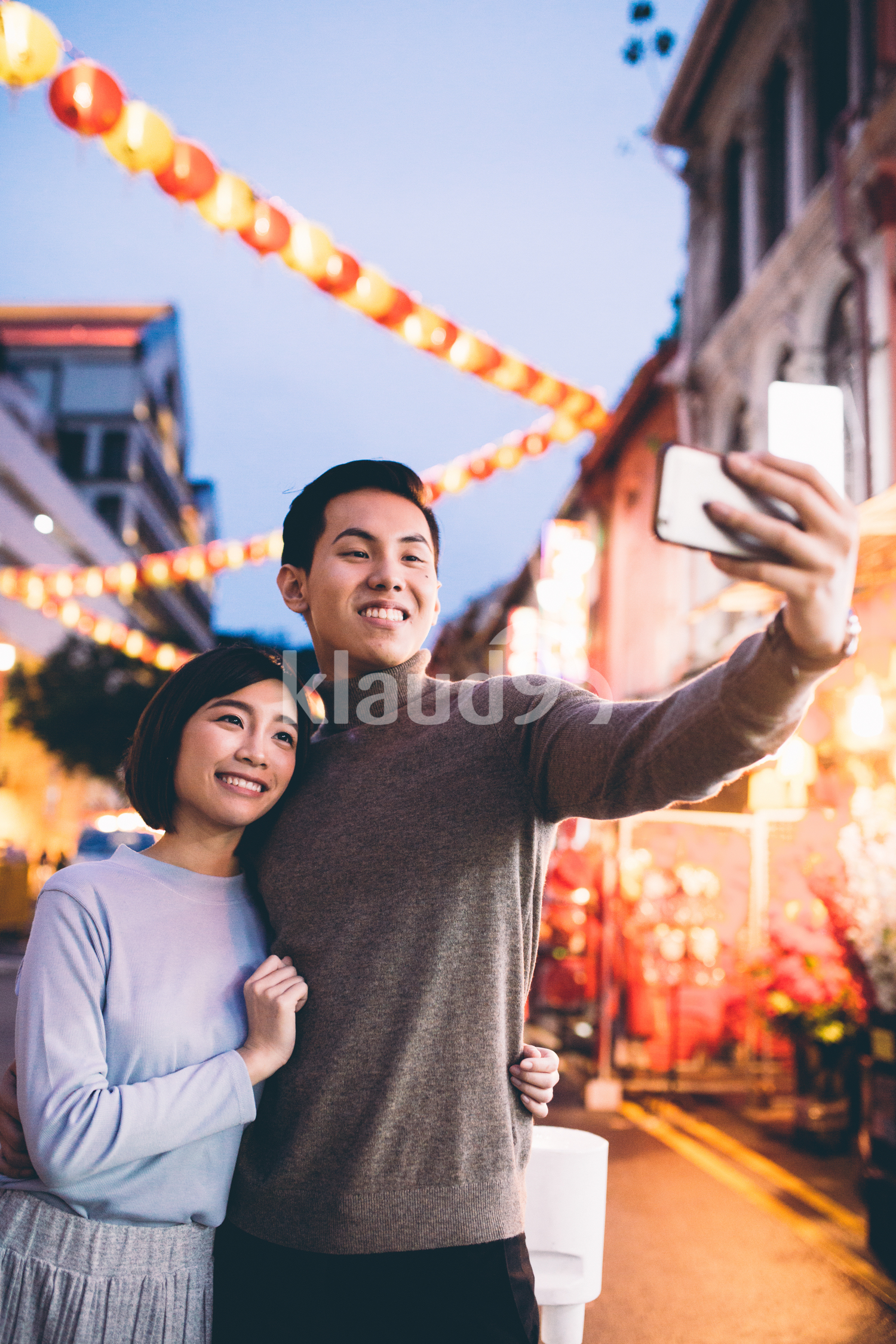 Bautiful young couple doing a selfie in Chinatown, Singapore during dusk