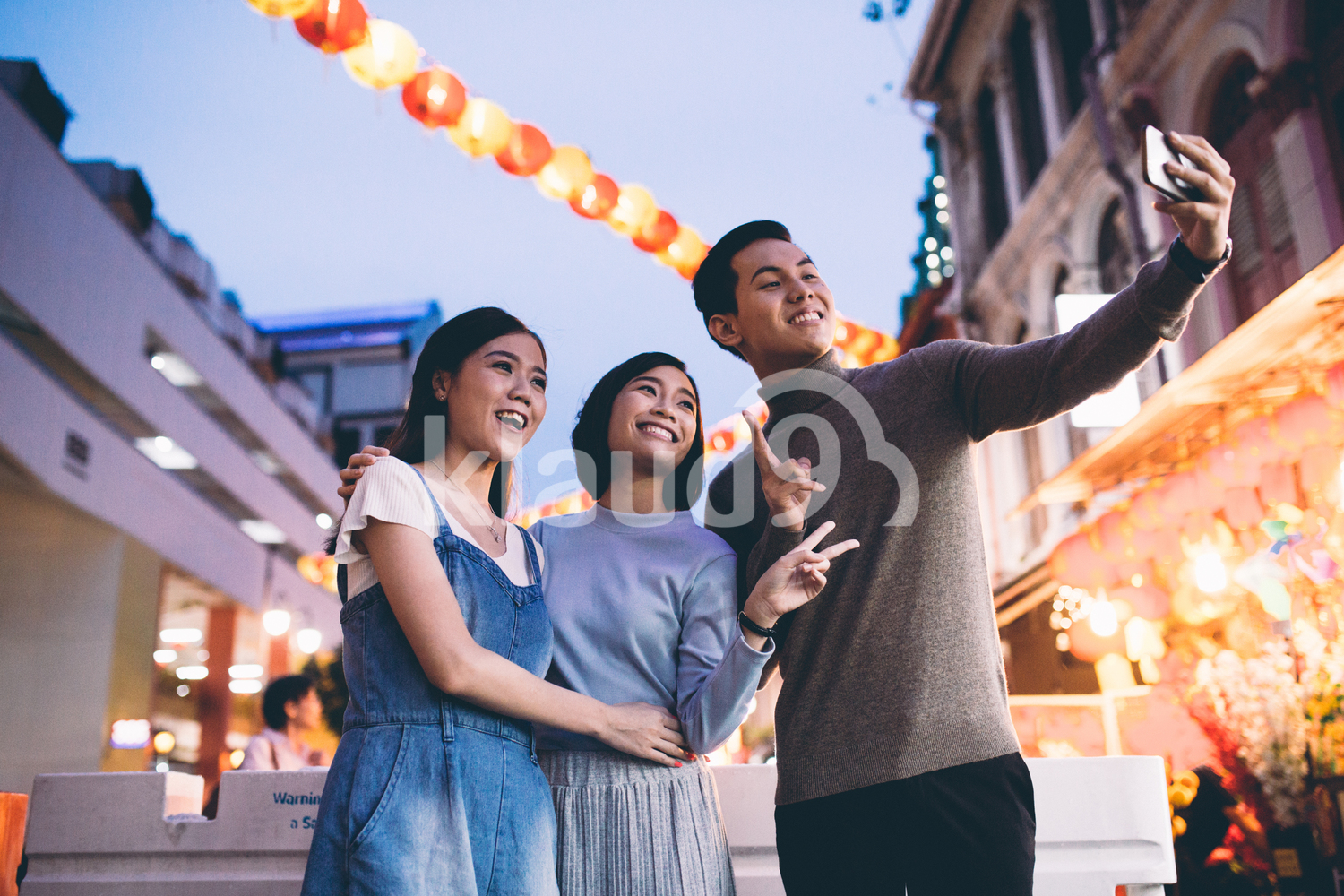 Beautiful young friends doing a selfie in Chinatown, Singapore during dusk