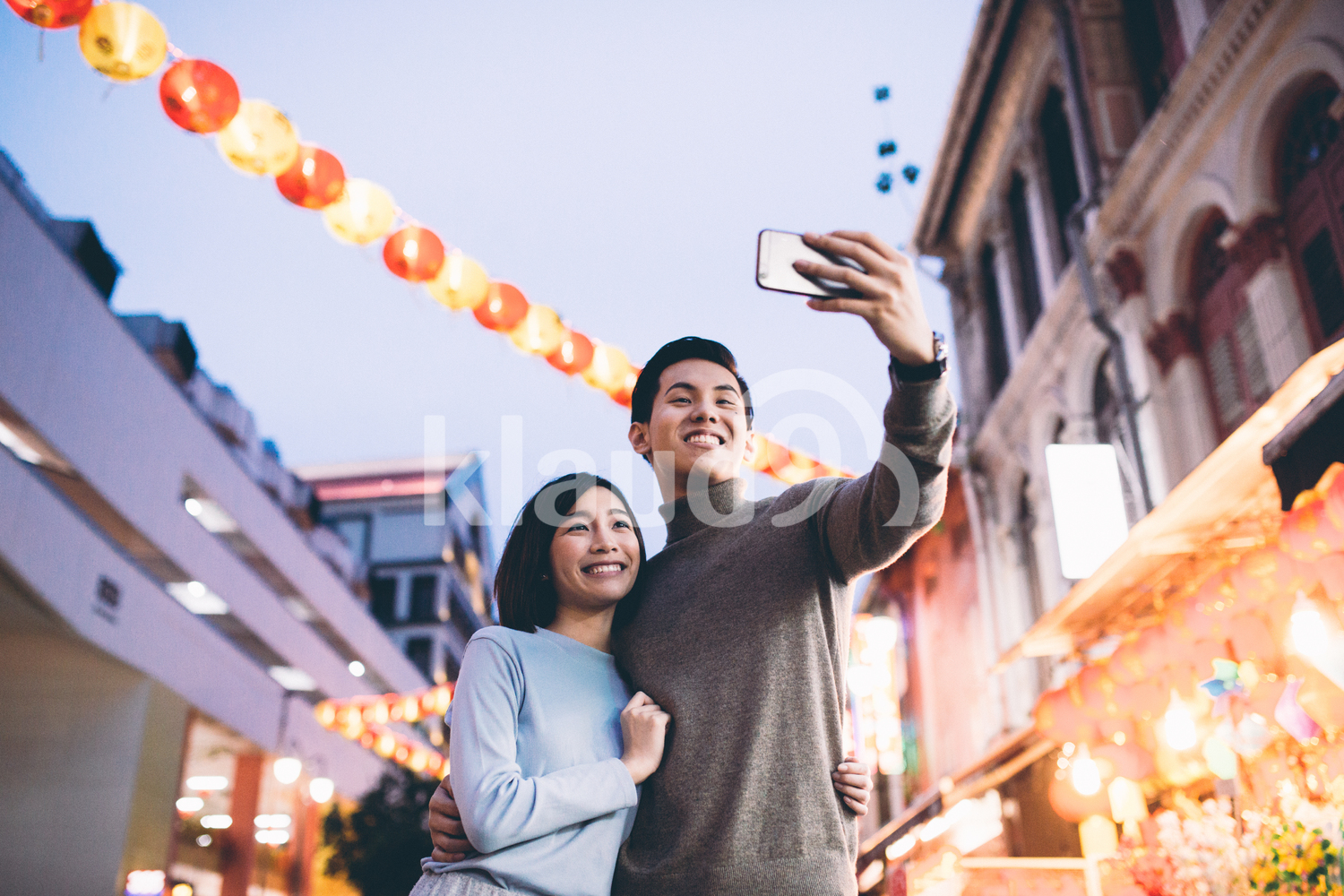 Young couple doing a selfie in Chinatown, Singapore during dusk