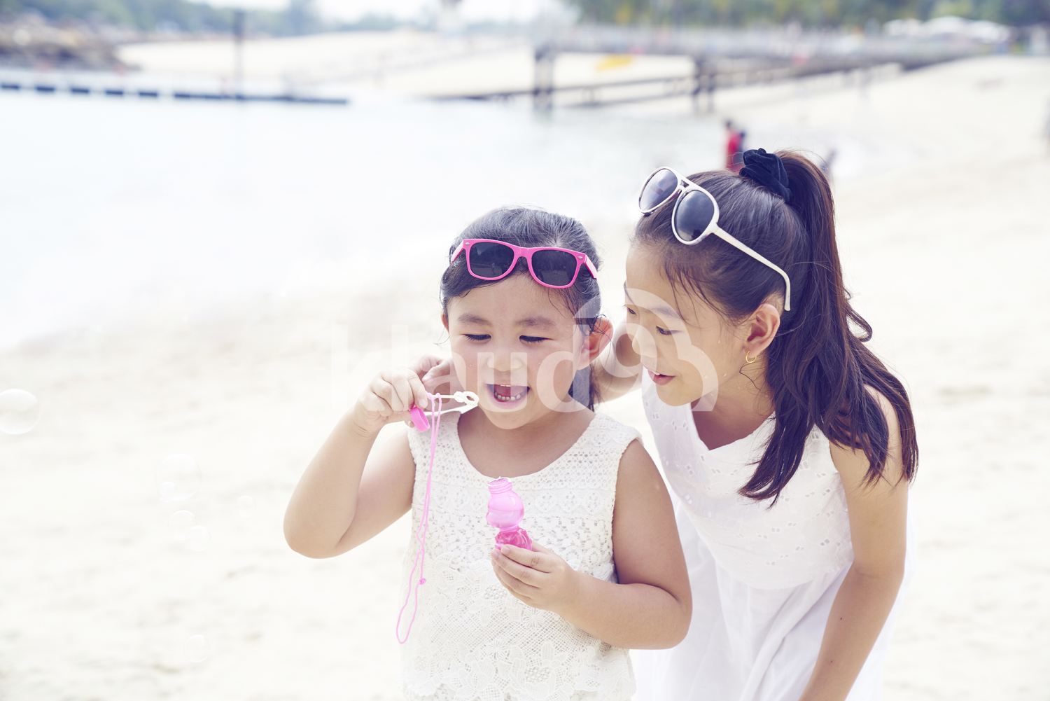 Portrait of adorable daughters playing with bubbles on Sentosa beach
