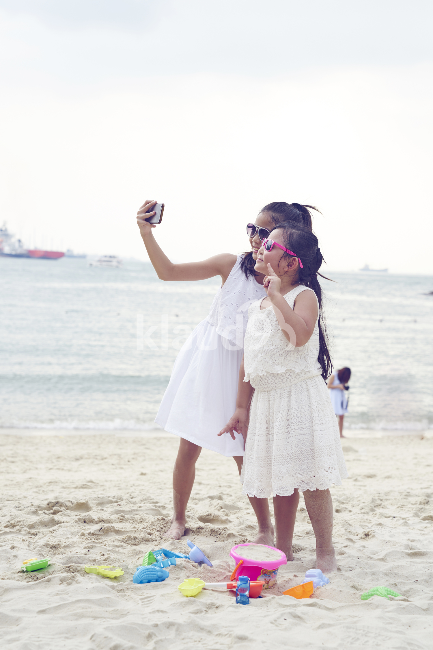 Cute siblings taking a selfie on Sentosa beach