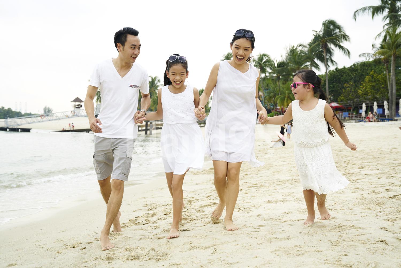 Family of four bonding and strolling on Sentosa beach
