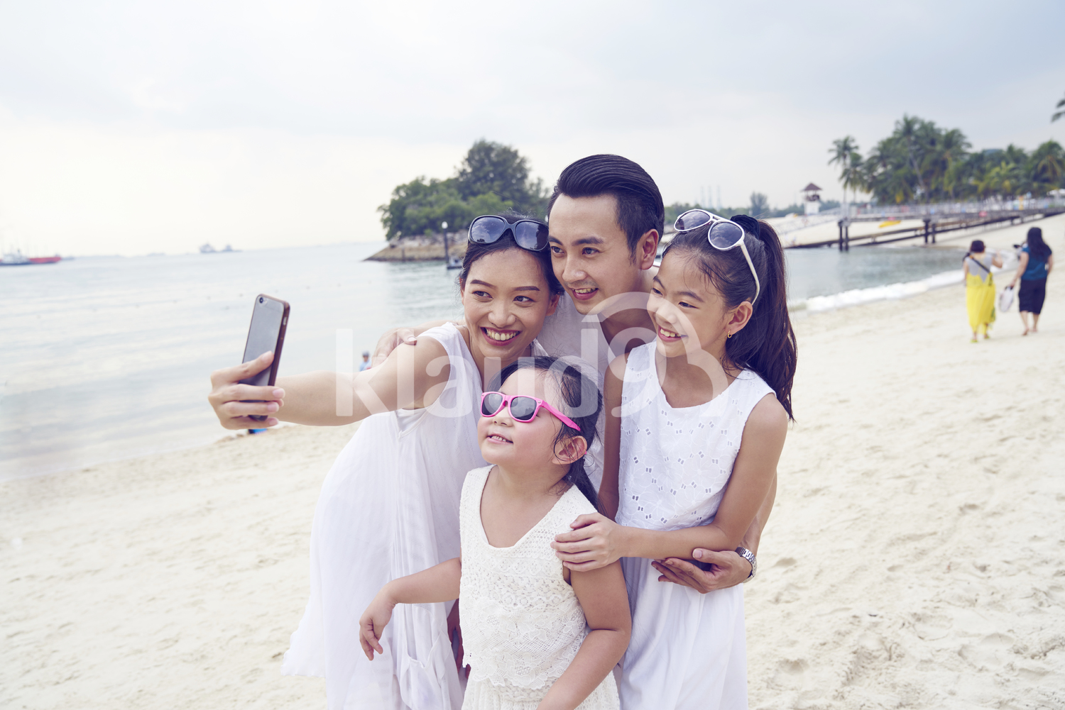 Cheerful family of four taking a selfie on Sentosa beach
