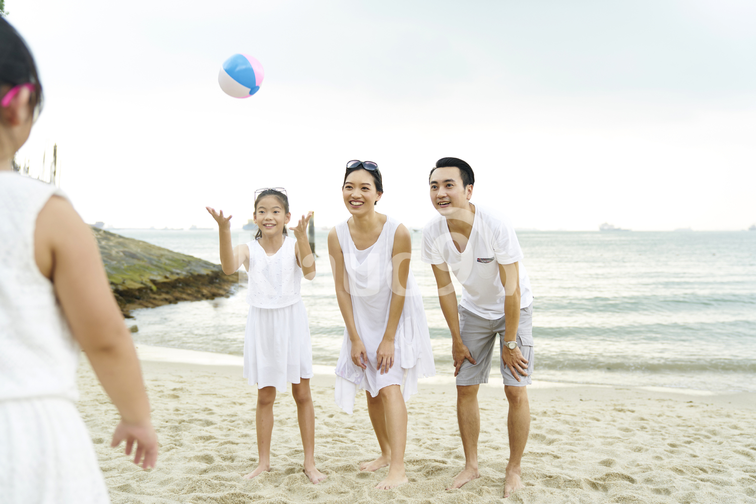Family playing with a ball on Sentosa beach