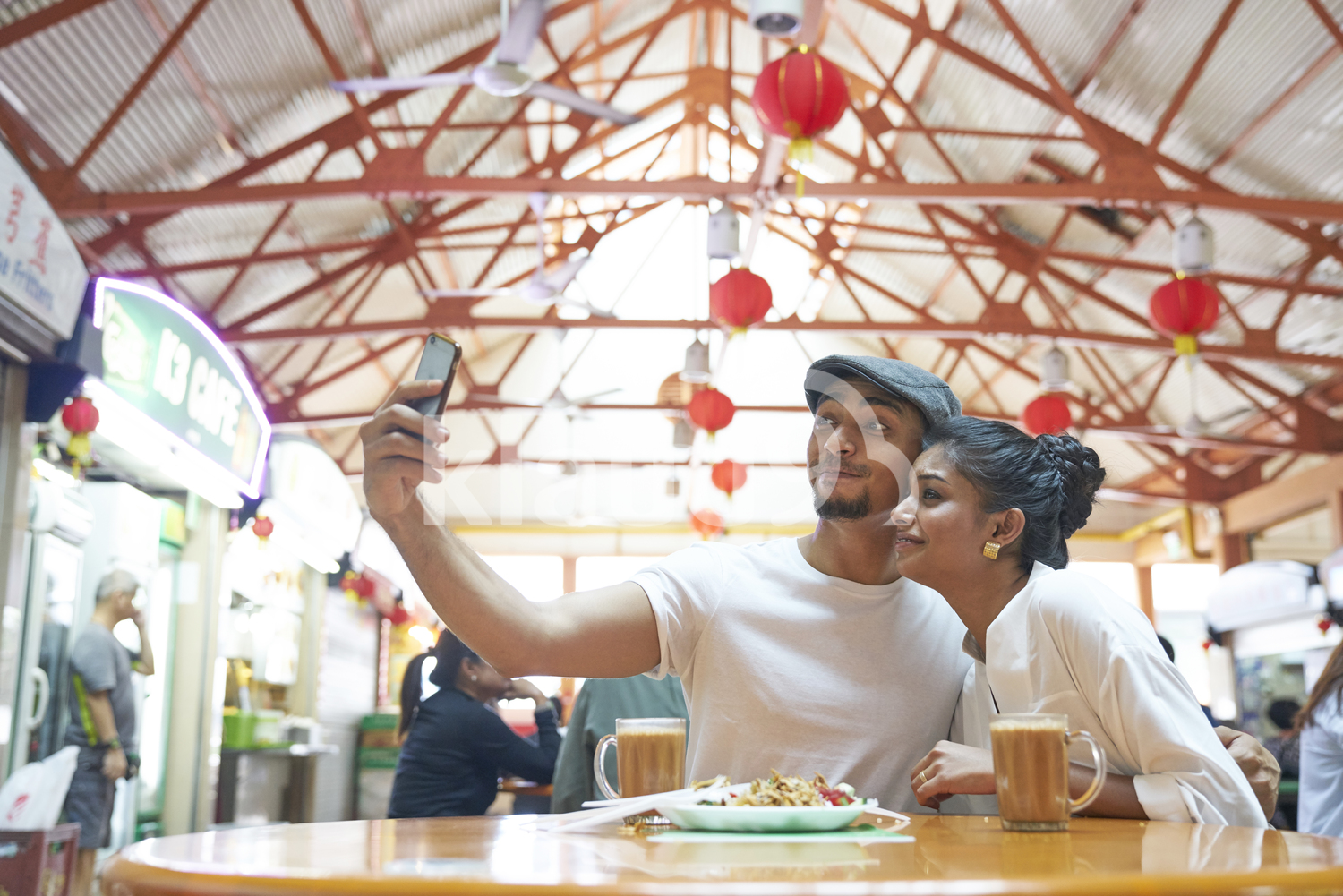 Cheerful young couple taking a selfie at Maxwell Hawker Centre, Singapore
