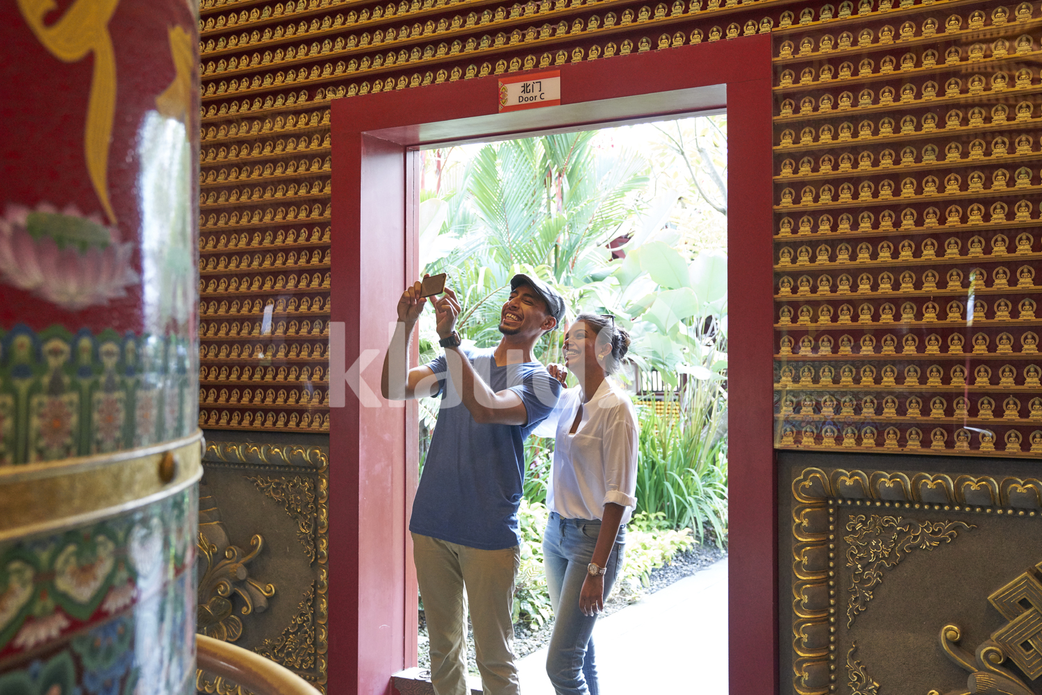 Curious tourists taking photos of a meditation bell in the Buddha Tooth Relic Temple