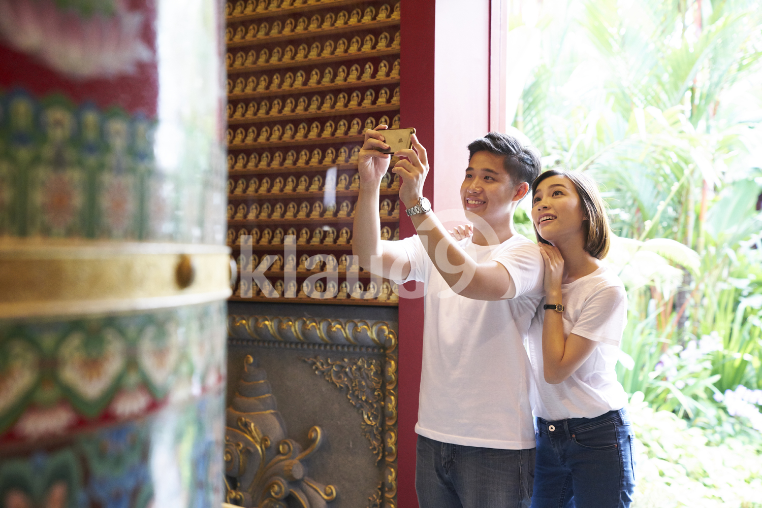 Young couple taking photos of a meditation bell in the Buddha Tooth Relic Temple