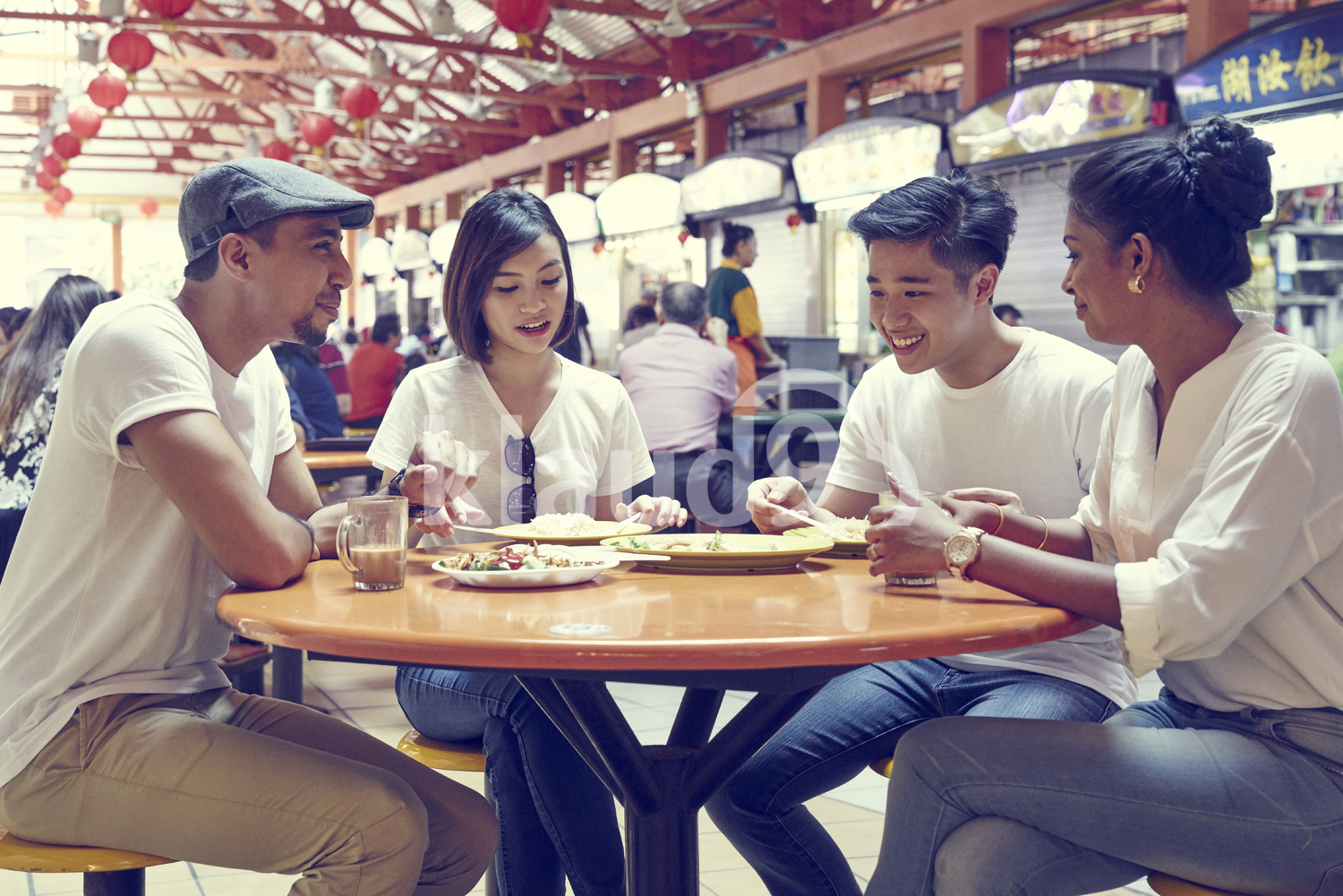 Group of friends having a meal at Maxwell hawker Centre, Singapore