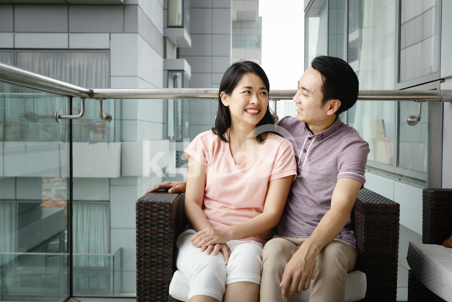Young couple cuddling on a condo balcony