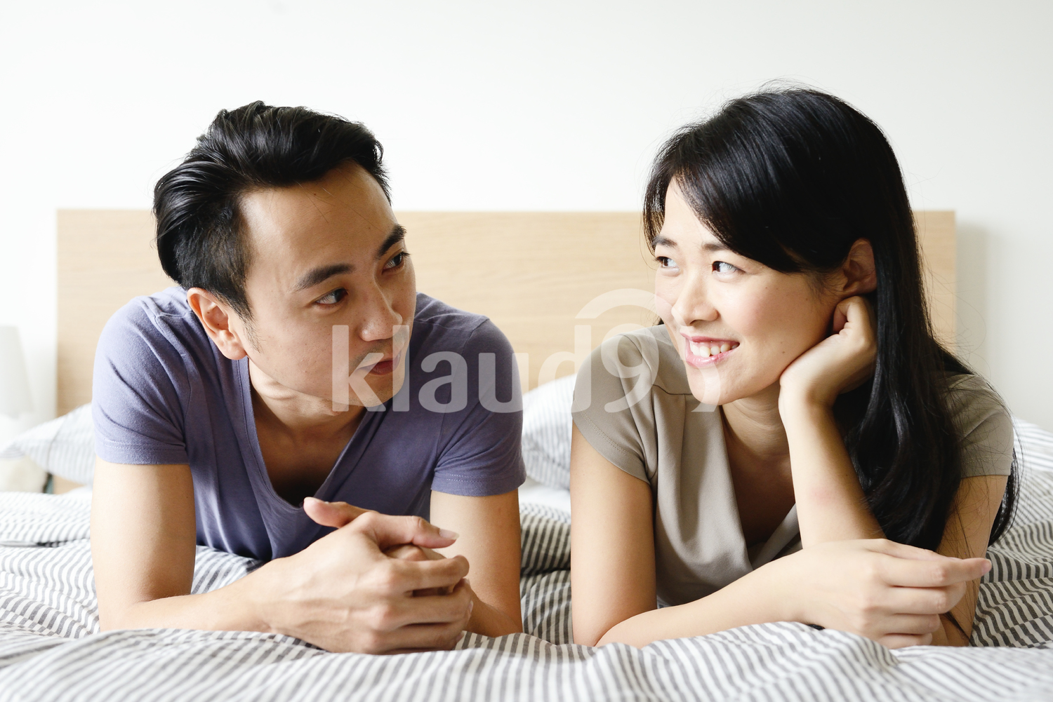 Young couple in bed chatting