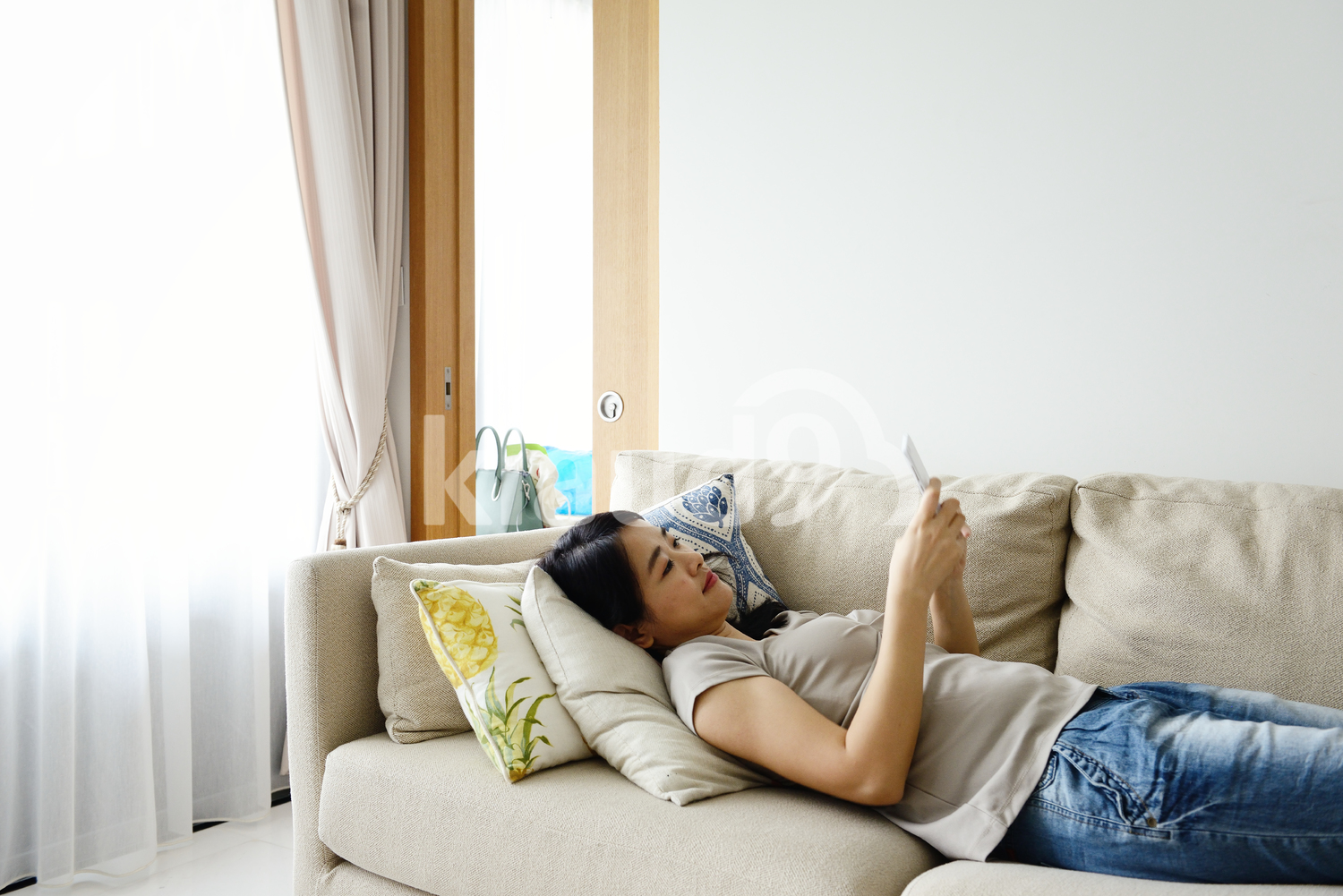 Young woman on a smart phone in a modern living room