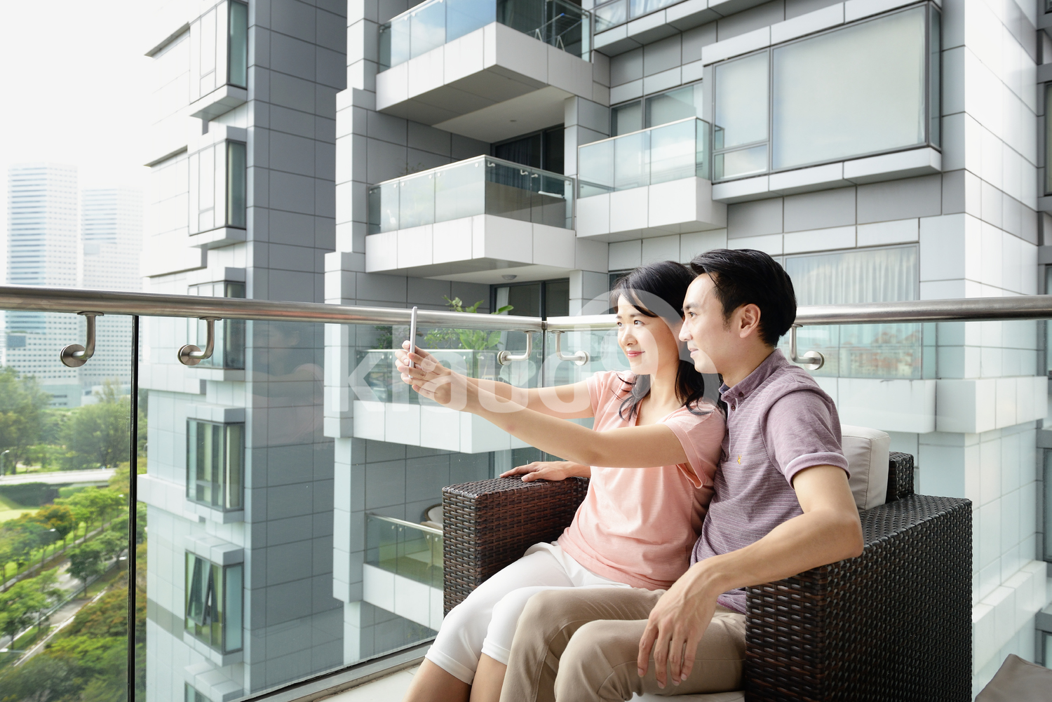 Husband and wife taking a selfie on a condo balcony