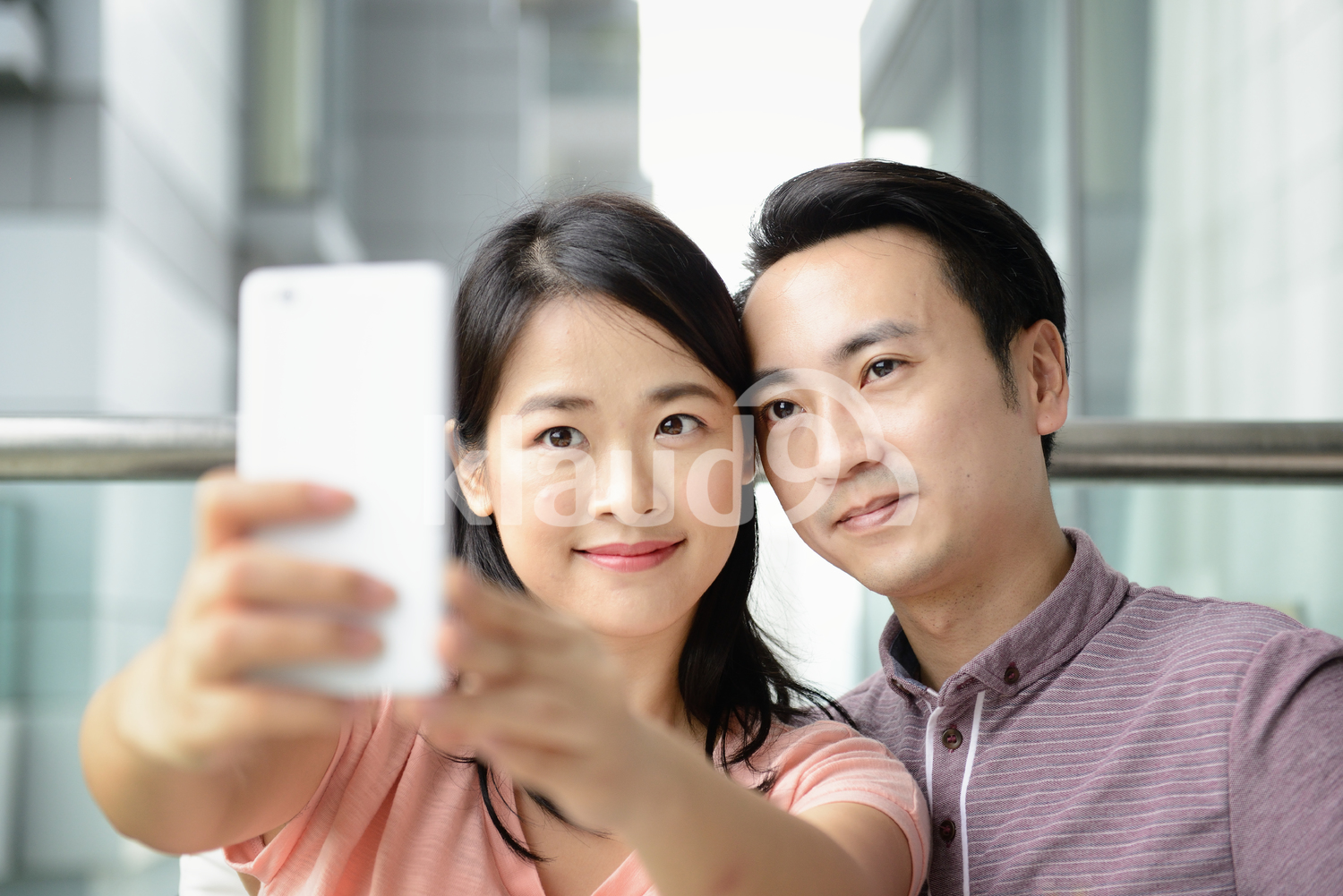 Young couple taking a selfie outside their new condo