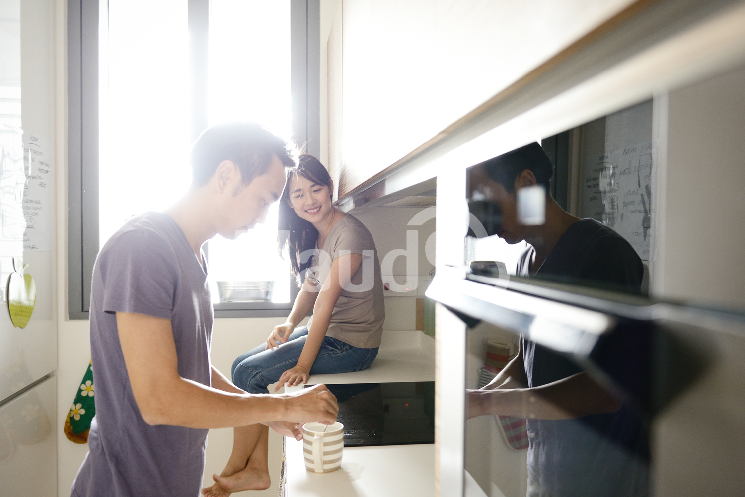 Young couple making morning coffee in their condo kitchen