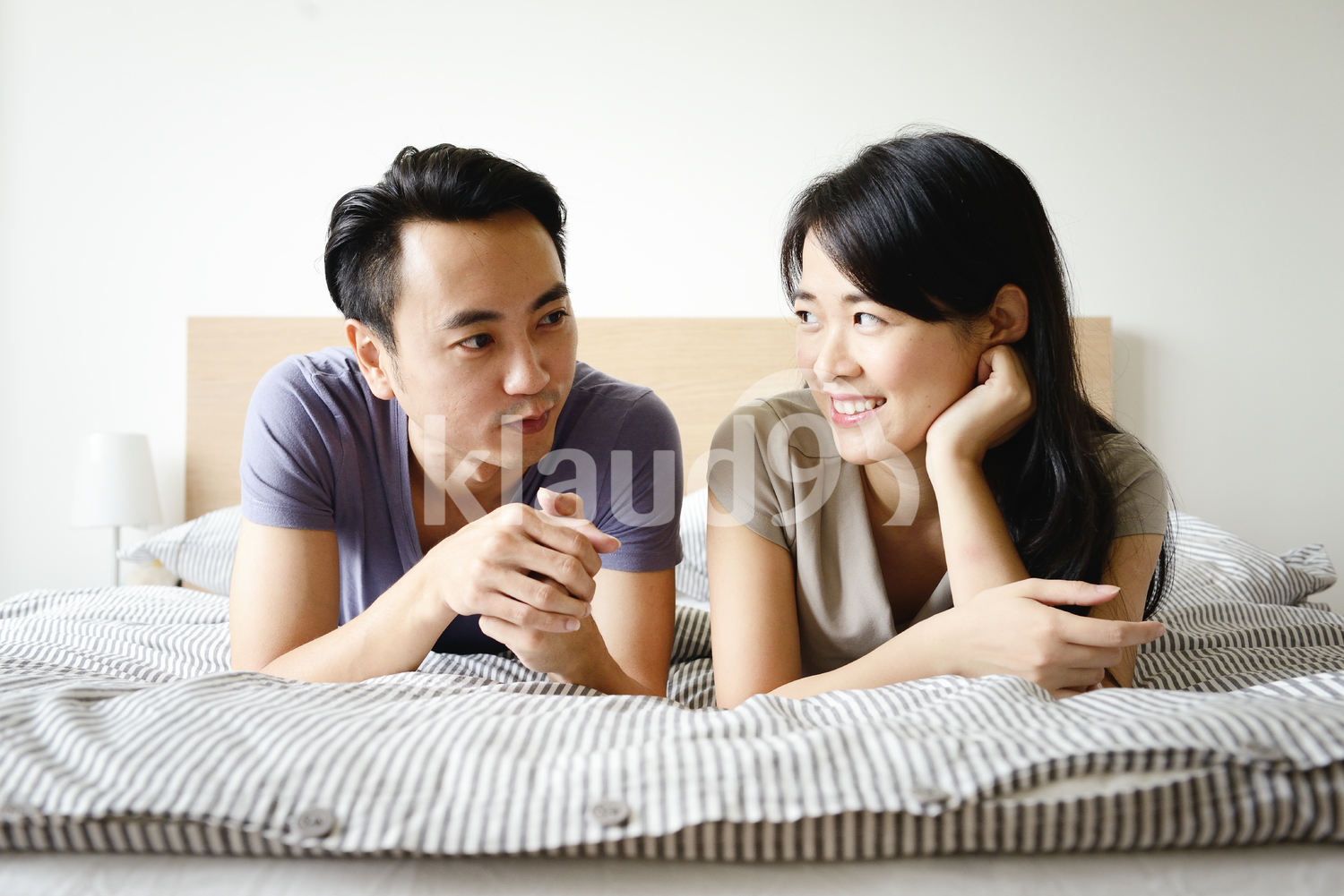 Young couple chatting in bed