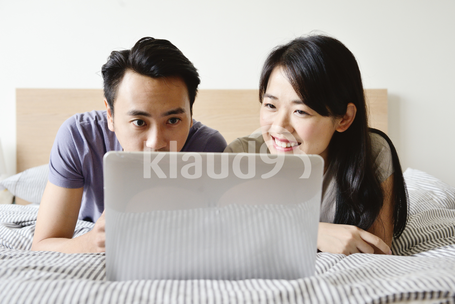 Husband and wife on a laptop together in bed