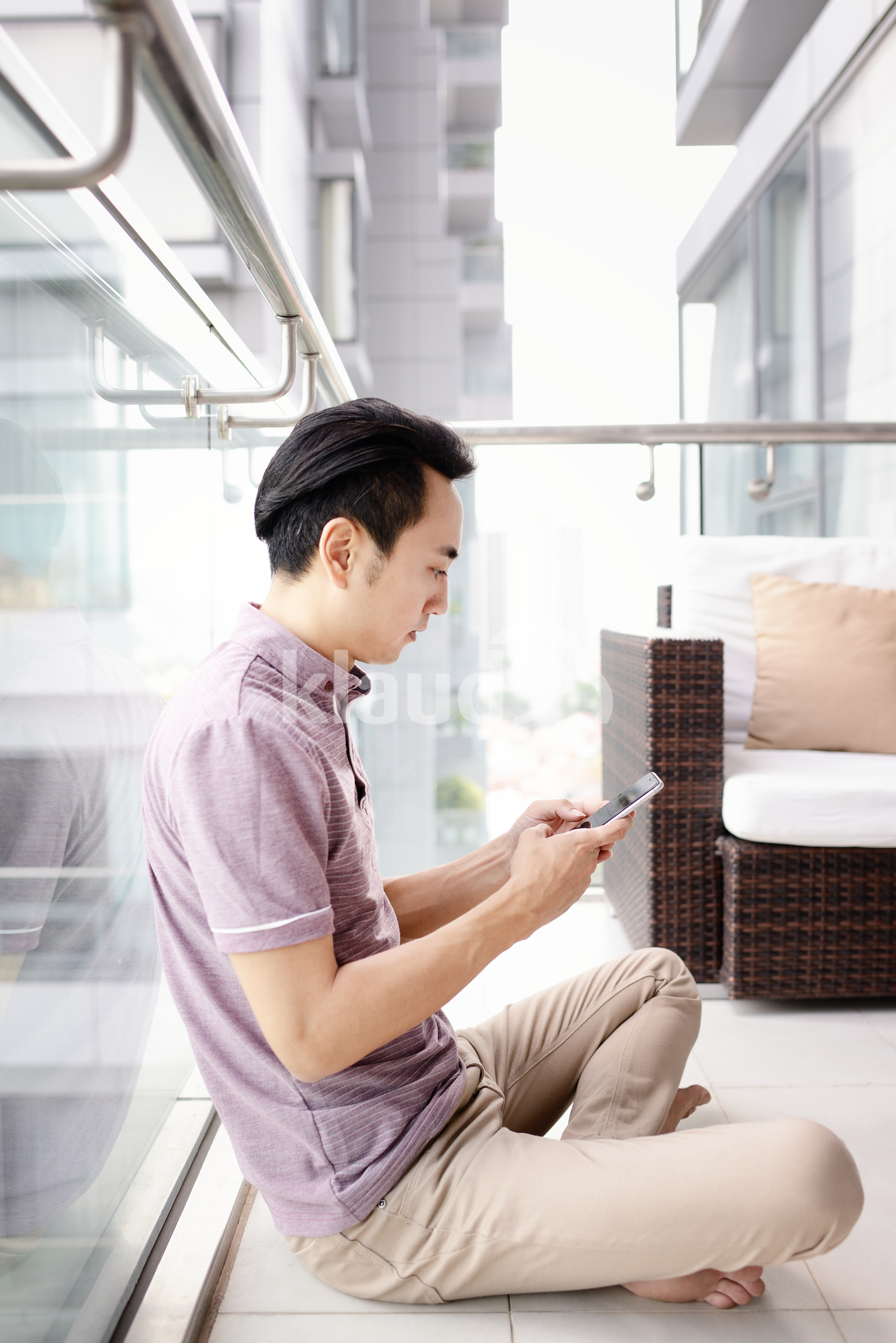 Young man reading from his smart phone on a condo balcony