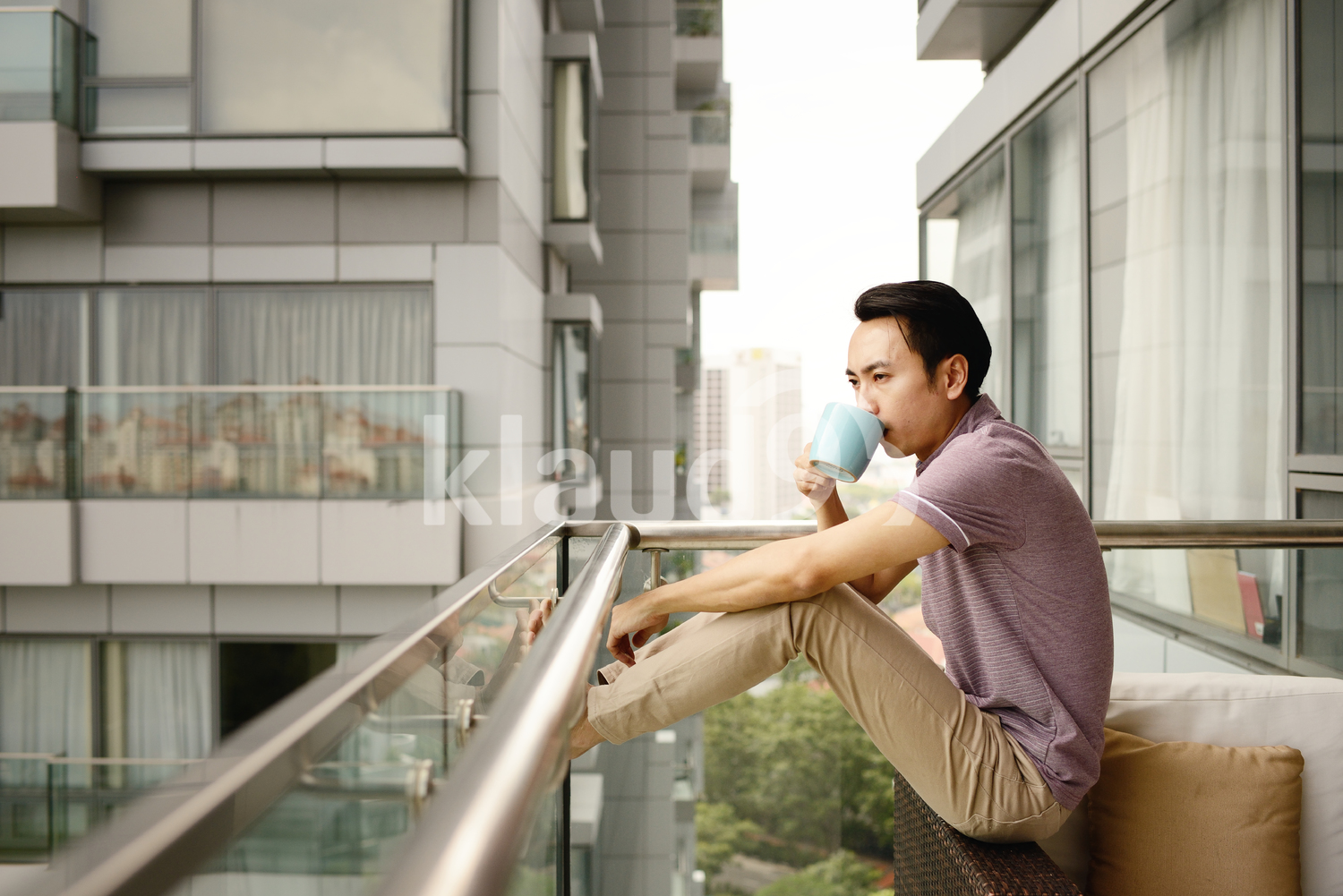 Young man drinking coffee on a condo patio in the morning