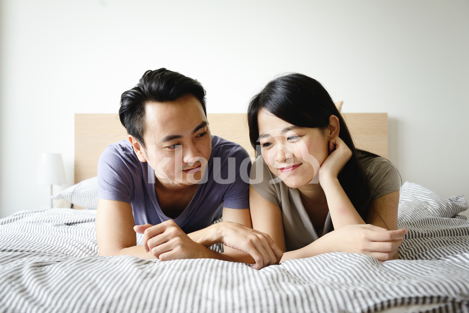 Young couple chatting in bed in the morning