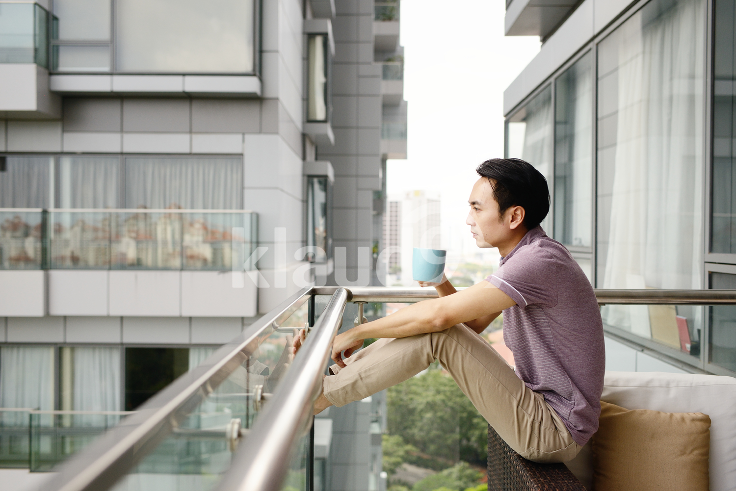 Young man drinking coffee outside a new condo