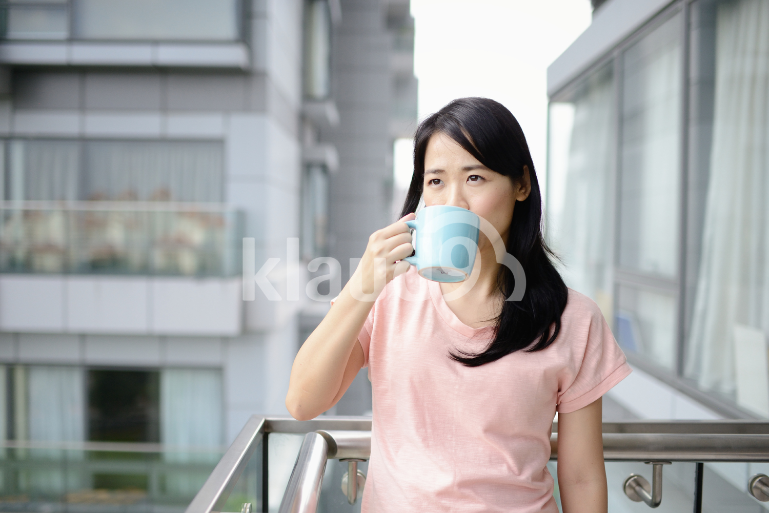 Young woman drinking coffee on a condo balcony