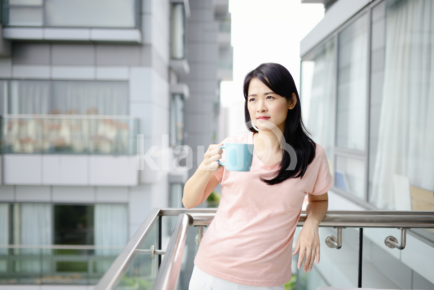 Confident young woman drinking coffee outside her new condo