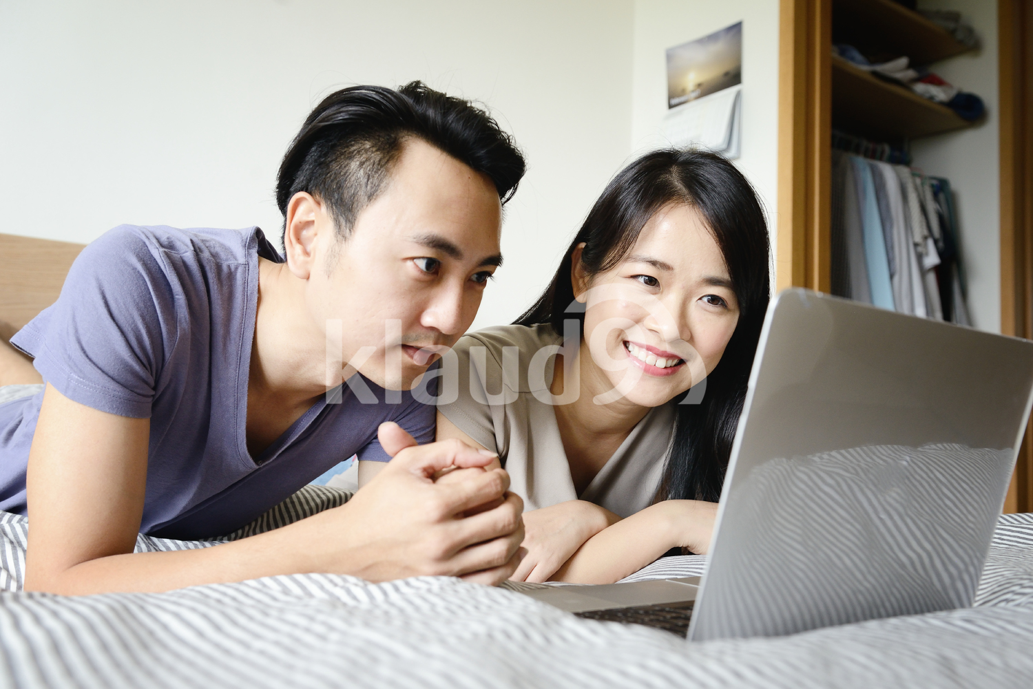 husband and wife in bed together on a laptop