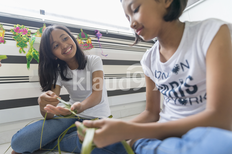 Young girl teaching her sister on how to make ketupat