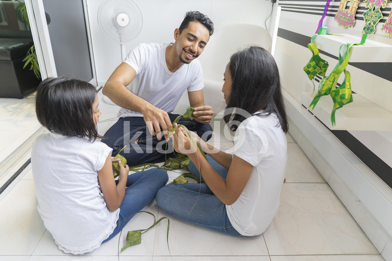 Young father teaching his kids how to make ketupat.