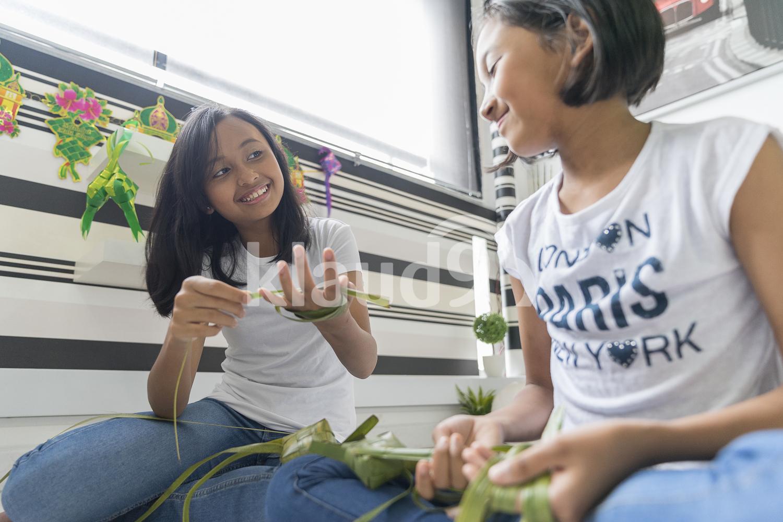 Young girl teaching her sister on how to make ketupat.