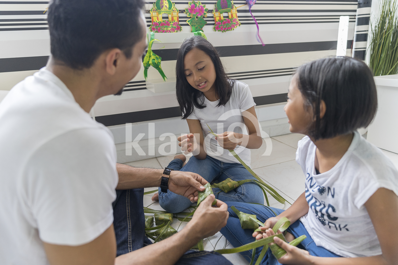 Family making ketupat
